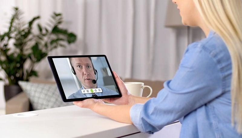 Una mujer rubia teniendo una videollamada con un ejecutivo de un banco